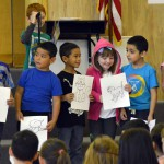 Photo of Oquirrh Hills students holding up drawings