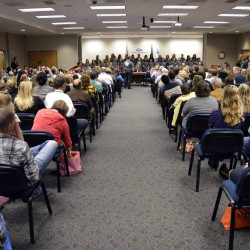 Photo of student choir singing at board meeting