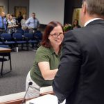 Jody Lynn Tolley shaking hands with superintendent during board meeting