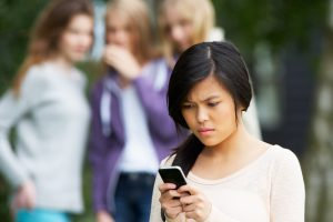 Teen girl looking grimly at phone while girls in background snicker