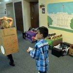 Orchard Elementary students line up in hallway with cardboard cars