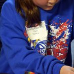 An Orchard Elementary student wears a name tag of a fictional immigrant
