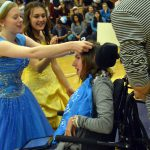Hunter High students place crown on the head of a girl in a wheelchair