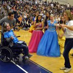 Hunter students applause as a proclamation is read to a girl in a wheelchair
