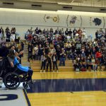 Teen in wheelchair waves to Hunter High students