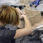 Student sculpting with ceramics
