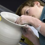Student sculpting wheel thrown ceramic piece