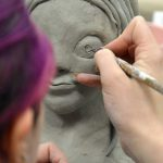 Student sculpting piece of clay
