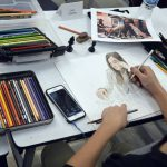 Student drawing with colored pencils