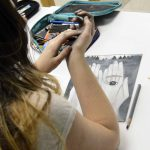 Student pauses while working on drawing