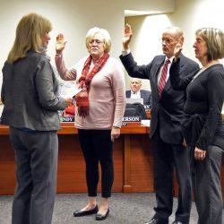 Three board members reciting the oath of office during board meeting