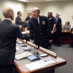 Police officers shaking hands with board members