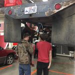 Students look under a truck hoisted on a lift
