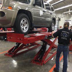 Student operating automotive lift