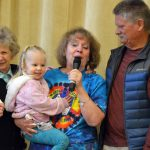 Hartvigsen teacher speaks into microphone surrounded by family