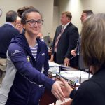 Skyline student shakes hands with board member