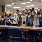Skyline girls basketball team poses with trophy at board meeting