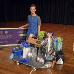 Bennion Jr High student poses with gifts from business partners