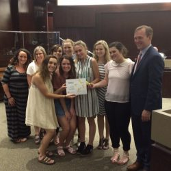Skyline High students hold up award with Salt Lake County mayor