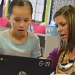 Rolling Meadows teacher and student work on laptop