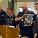 Hunter High teacher holds plaque standing next to administrators and guests