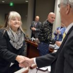 Outstanding classified employee award recipients shake hands with board members