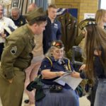 Veterans and individuals dressed in old military uniforms at Granite Park Jr High