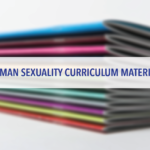 Stack of booklets with text 'Human Sexuality Curriculum Materials'
