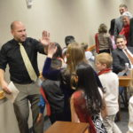 Teacher gives high fives to students