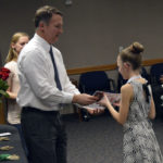Superintendent Bates hands a ribbon to a student