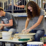 Student artists using wheel thrown pottery