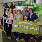 Upland Terrace teacher holding large 'winner' poster