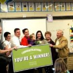 Bennion teacher holding large 'winner' poster