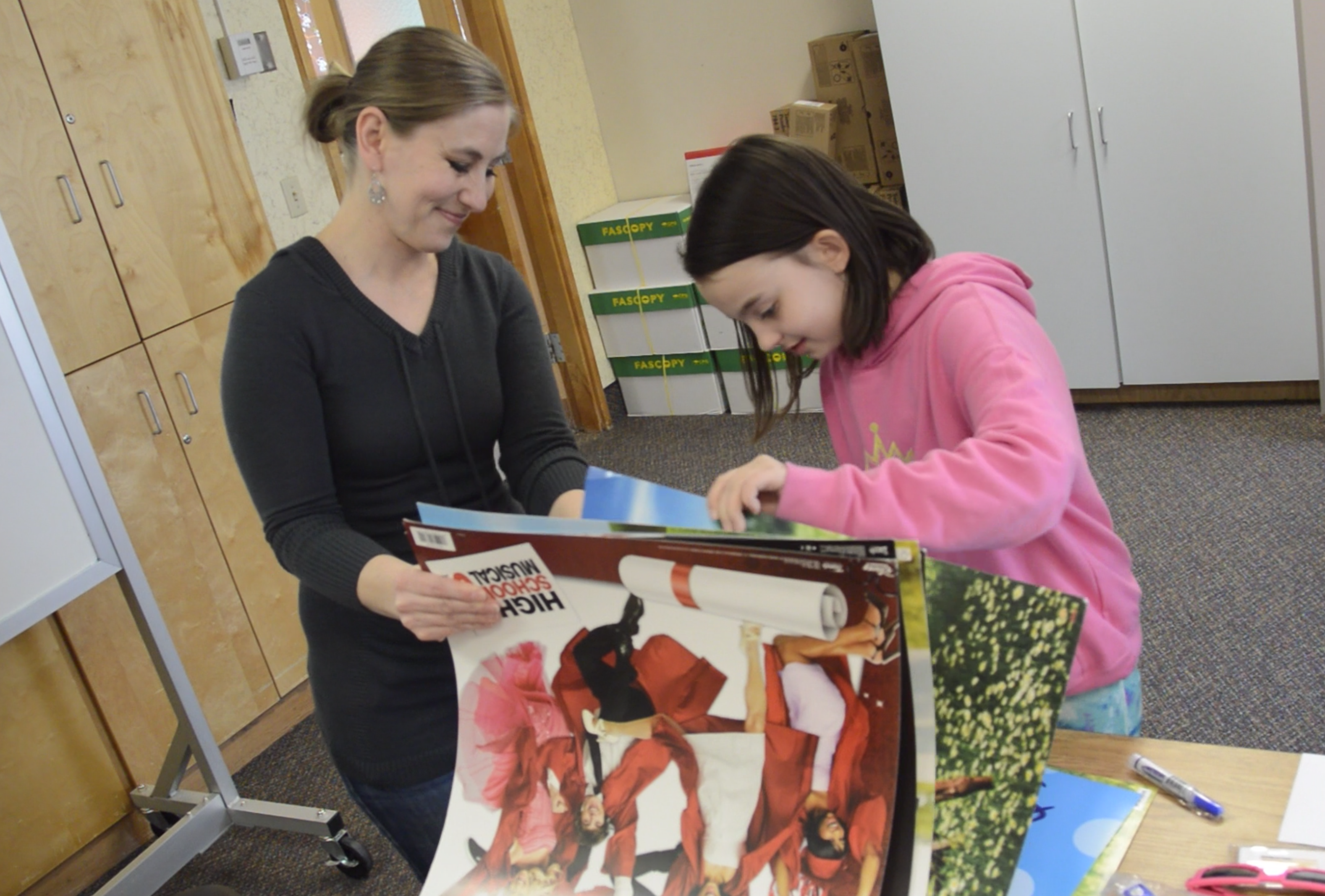 West Kearns volunteer and student look through posters