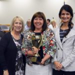 Rolling Meadows staff holding trophy for highest MGP