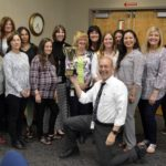 Monroe Elementary staff holding trophy for highest MGP