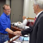 Jacob Smith shakes hands with board members