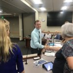 Utah legislator shakes hands with board members