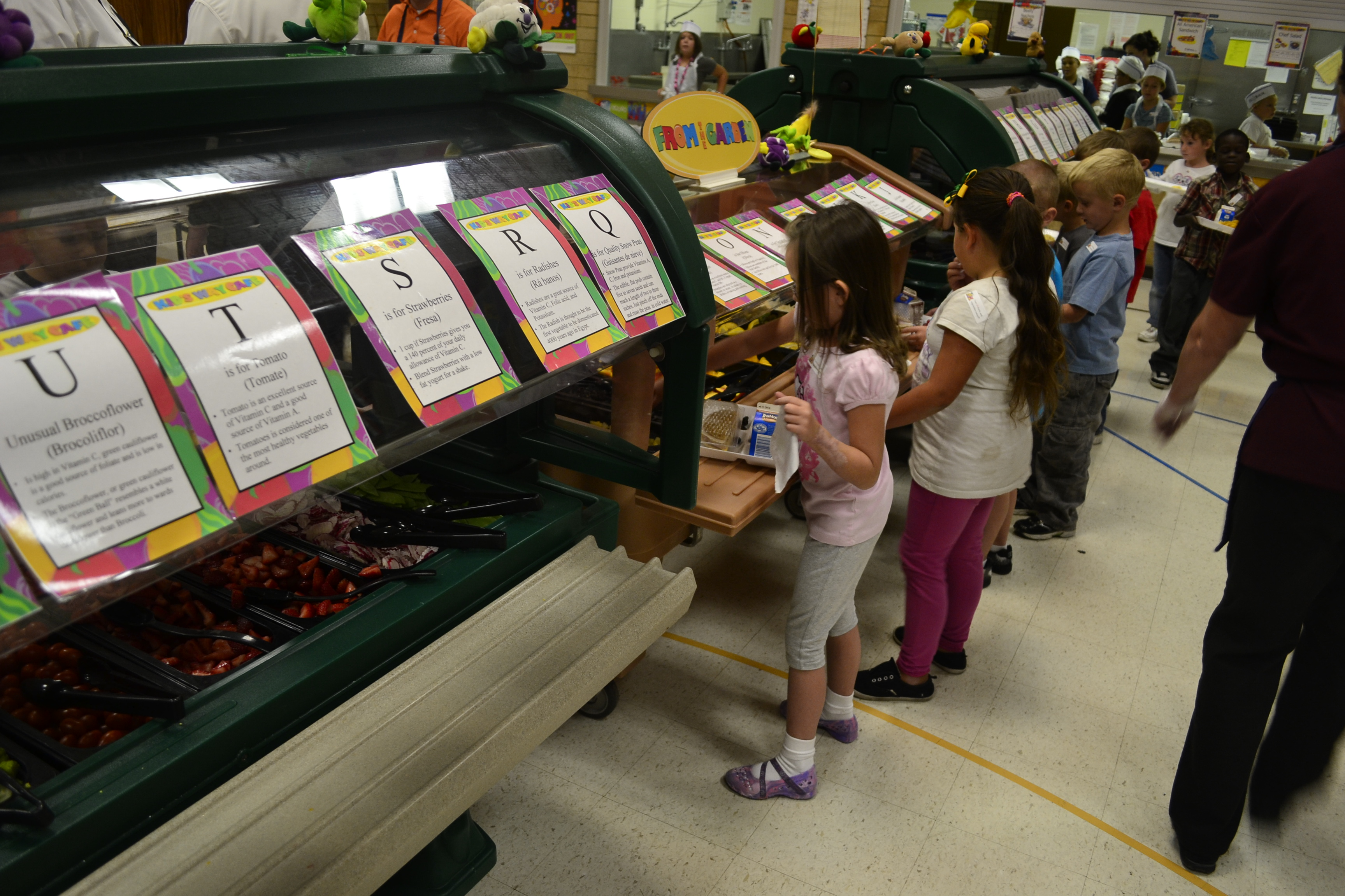 Students fill their lunch trays at a food cart