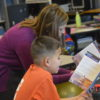 Elementary teacher reads aloud with student