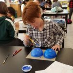 Evergreen student painting Christmas tree ornament