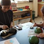 Evergreen students painting Christmas tree ornaments