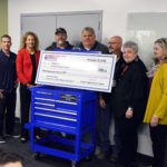Construction trades teachers hold large check from Harbor Freight