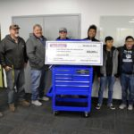 Construction trades teachers and students hold large check from Harbor Freight