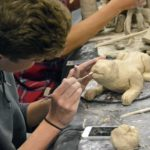 Student sculpting animal from clay