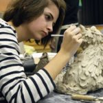 Student creating clay scultpure