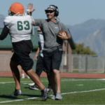 Kearns High coach high-fives football player