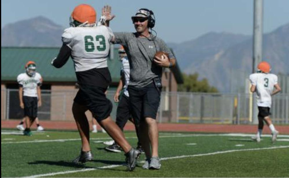 Kearns High coach high-fives football player