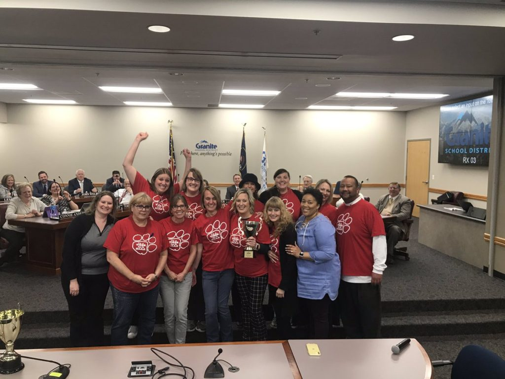 Roosevelt staff holding trophy at board meeting