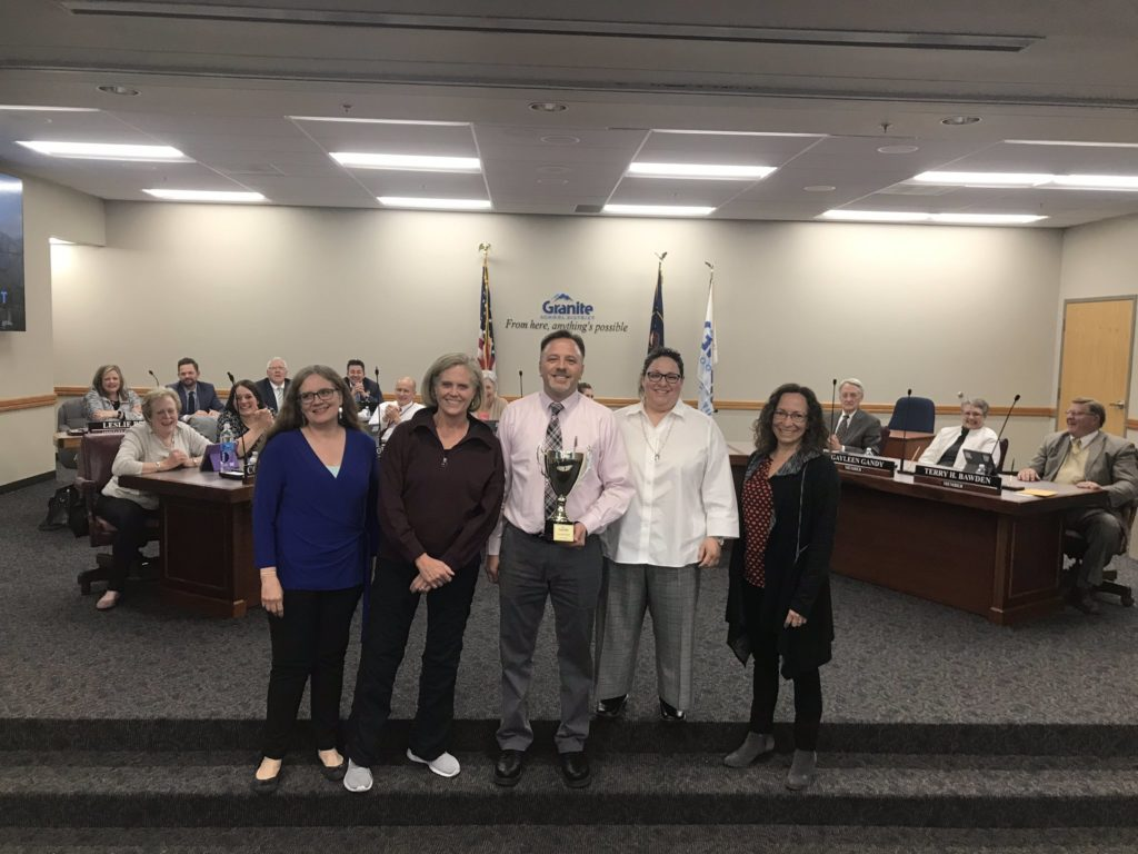 Robert Frost Elementary staff holding trophy at board meeting